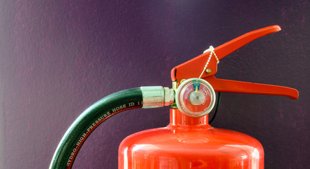 suppression: Close up of fire extinguisher handle and hose