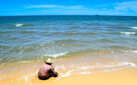 digging: Elderly lady digging for sheels at oceanside Stock Photo