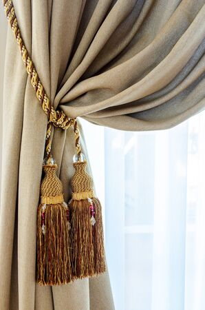 magnificence: Dual tassels on curtain at main window Stock Photo