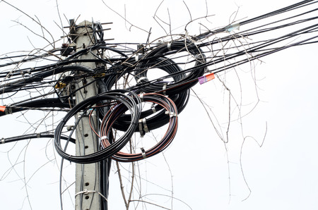 tangling: Assortment of cables jumbled and fixed to pole Stock Photo