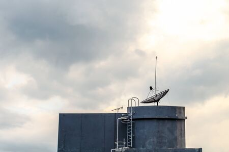 Satellite dish on top of rooftop water tank
