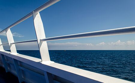 Close up white railing ferry boat against blue sea Foto de archivo