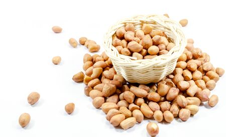 Close up of raw peanuts in basket on white background 免版税图像