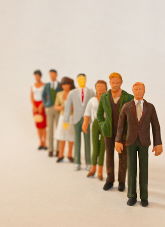 People figurines standing in line Banco de Imagens
