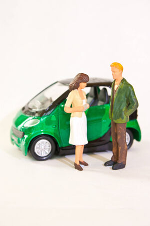 Man and woman figurines standing outside the car