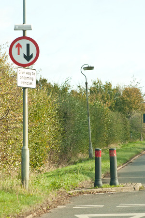 one lane road sign: A give way to oncoming traffic sign alongside bollards on a typical British road Stock Photo