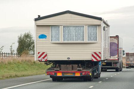 도로에 움직이는 트럭 위에 집 스톡 콘텐츠