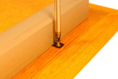 screwing: Close up of a screwdriver screwing a screw on a box frame