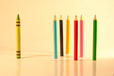 Single crayon standing alone among the standing colour pencils
