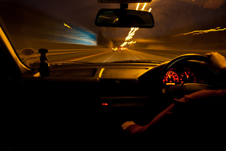 slow lane: Car passengers point of view of a car driving in the dark Stock Photo