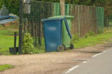 recycle area: A blue and green recycle bin on a roadside in the United Kingdom