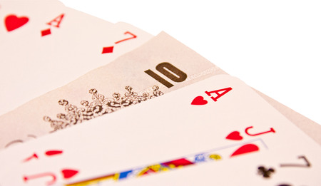 hold em: A ten pound note in between a spread of poker cards Stock Photo