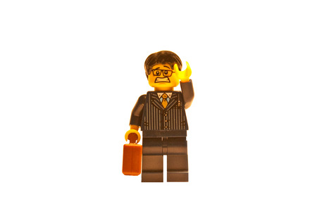 Lego business man with a worried expression lifting an arm up