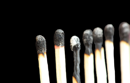 A row of standing burnt matches on black background photo