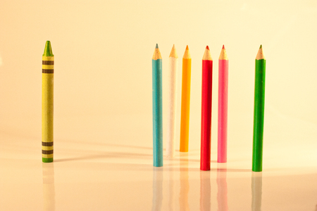 A concept of victimisation with a single coloured crayon standing apart from coloured pencils. Stock Photo