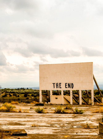 An old cinema billboard has the deep words of The End painted onto a blank board, in a degraded parking lot. Фото со стока