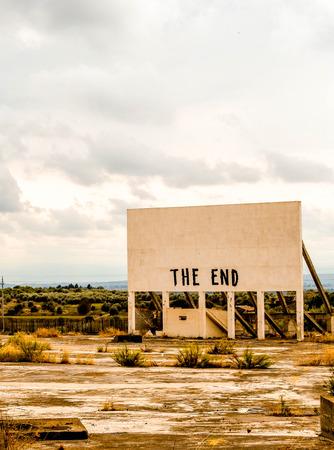 Een oud bioscoop-billboard heeft de diepe woorden van 'The End' geverfd op een leeg bord, op een versleten parkeerplaats. Stockfoto