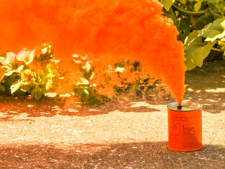 A bright orange smoke grenade used to signal in the event of rescue or to show a position from far away. Imagens - 87269447