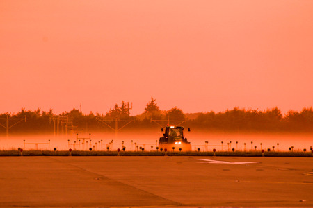 A tractor seen in amongst the mist, cutting the grass around the runway of a busy airport, before air traffic begins to arrive and depart. Stock Photo