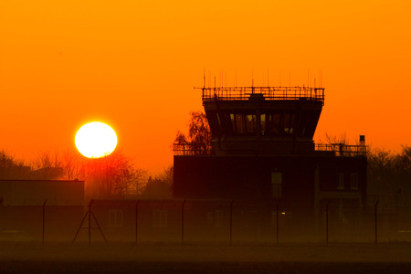 A beautiful view across an airport Air Traffic Control tower as the sun rises in the background.