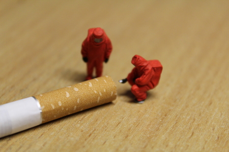 criminal: Two people in chemical suits inspect a cigarette.