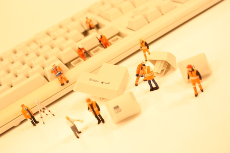 A close up view of miniature plastic figures working on a computer keyboard. Foto de archivo