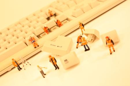 Una vista de cerca de figuras de plástico en miniatura que trabajan en un teclado de computadora. Foto de archivo - 89459443