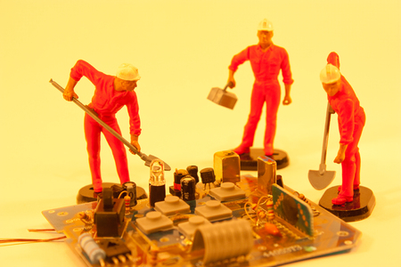 A team of skilled electrical engineers work together to repair broken components. Stock Photo