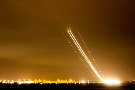 A view across a busy airport at night.
