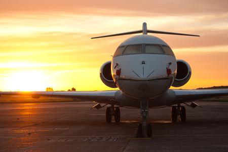 Un avión de pasajeros / privado contra un amanecer / atardecer.