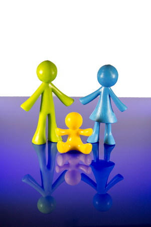 A family of plastic figures stand together.  A man, woman and baby as seen in the image. Stock Photo
