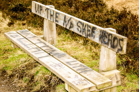 A wooden bench along a country walk that has been vandalised by disrespectful people. Stock Photo