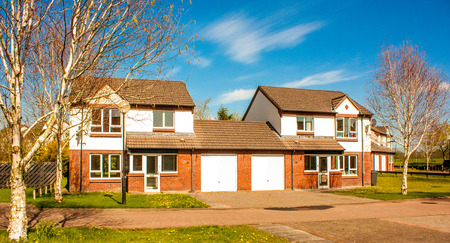 Une maison britannique typique, semi-détachée avec un garage et un jardin d'herbe à l'avant. Banque d'images