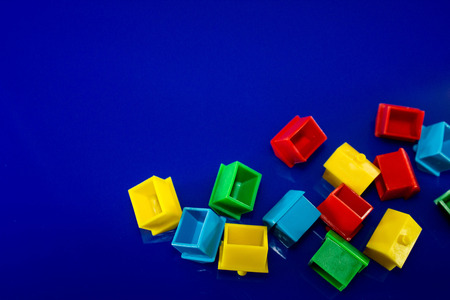A blue background with plastic houses as the main focus.