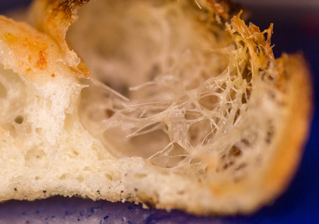 A look inside the crust of a pizza.  The strings tying up the sides etc of the crust within.