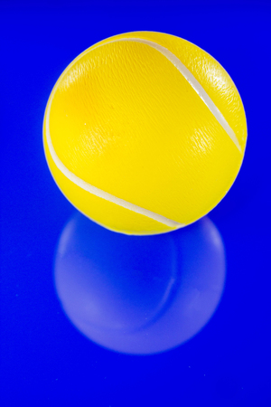 A closeup of a bright yellow tennis ball against a reflective blue background.