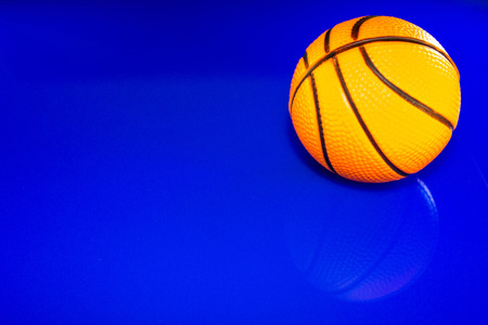 A closeup of a basketball, against a reflective blue background.