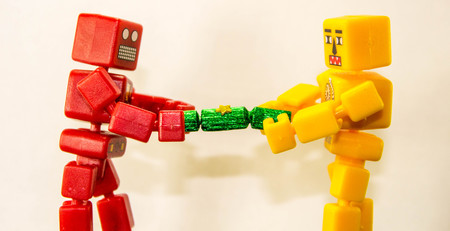 Two robot people battle to win at pulling a Christmas Cracker. Stock fotó