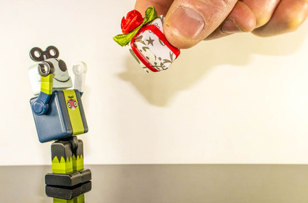 A small robot person receives a gift from a human.