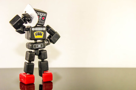 A robot stands with their hand on hip whilst they use their smart phone.