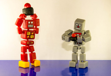 Two robots stand holding their Nuclear Buttons comparing size. Stock Photo