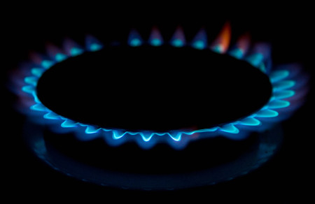 A bright neon blue flame emitting from a cooker hob. Reklamní fotografie