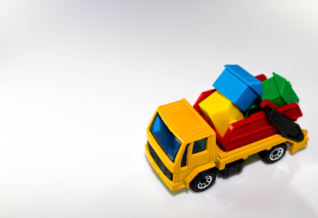 A skip lorry with a skip on the rear, full of coloured property.