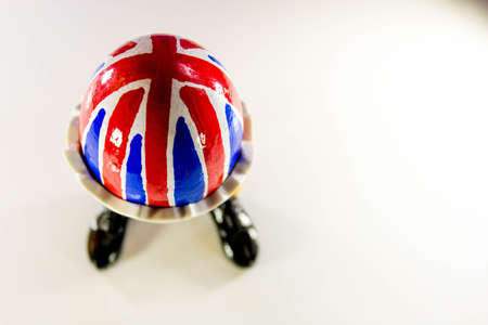 A British flag egg in a novelty egg cup, with legs.