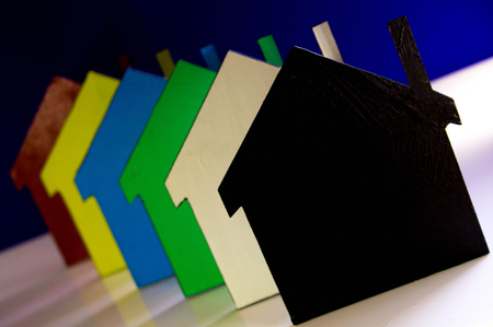 A stack of coloured houses against a plain background.