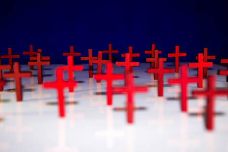 Christian crucifix crosses standing on a solid colour background. Stock Photo