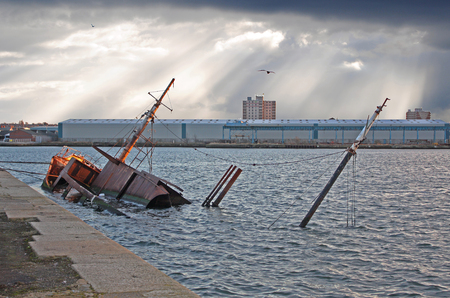 March 27, 2010 – Birkenhead Dock, Liverpool, England, United Kingdom. An old rusty ship sunken inside the harbour area, against the dock wall. The morning sun rising behind the buildings.