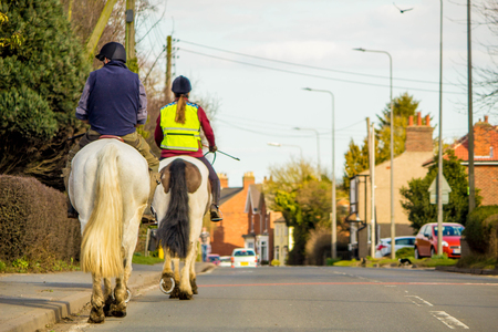 Two horse riders travel through a small village, on the main road.