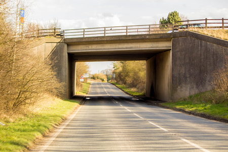 A typical British road leading under a small bridge. The road leading round to the right in the distance, being empty of other traffic. Zdjęcie Seryjne