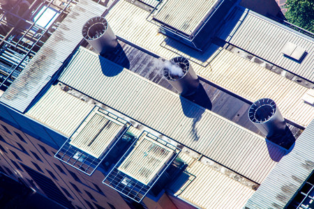 A view from above, looking down onto an industrial rooftop where chimneys expel steam.